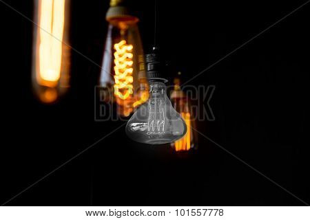 Hanged  Orange Decoration Light Bulbs  In Dark Room With Non-color In Middle Onw And The Others  Is