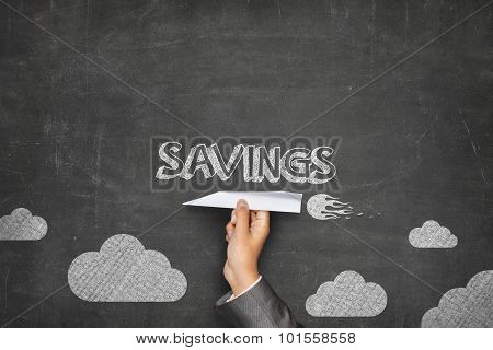 Savings concept on blackboard with paper plane