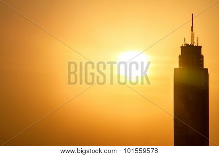 Big Sunset And Building At City With Transmission Towers