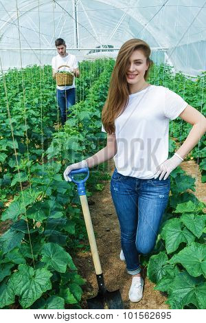 Farmer with shovel smiling directly at the camera