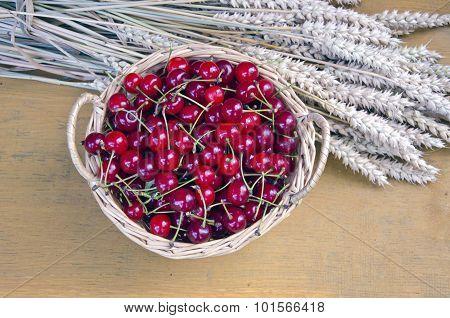 Cherries In Wicker Basket With Bundle Of Wheat