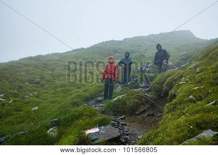 Hikers In Raincoats On Mountain