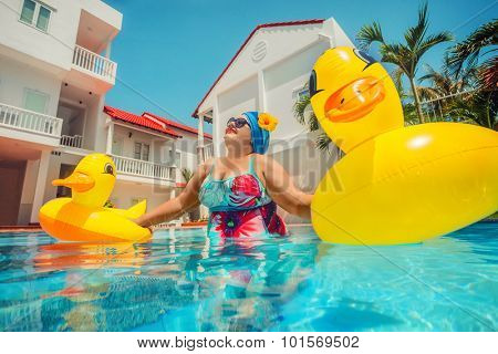 Beautiful young fat woman relaxing in the pool with yellow duck lifebuoy