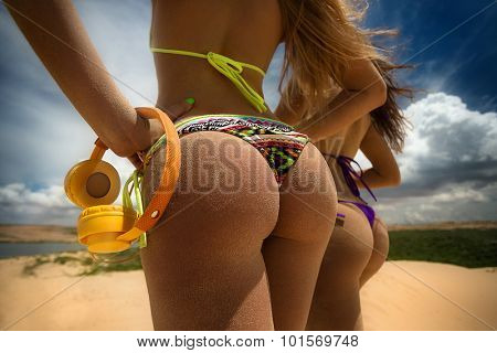 Photo of two girls in bikini on sandy dunes with headphones tanning in the bright summer sun
