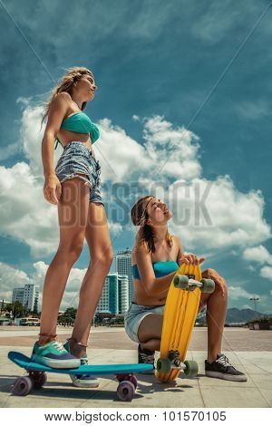 Portrait of beautiful skateboarding women on skateboards at summer park.