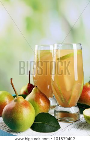 Fresh pear juice with fruit on bright background