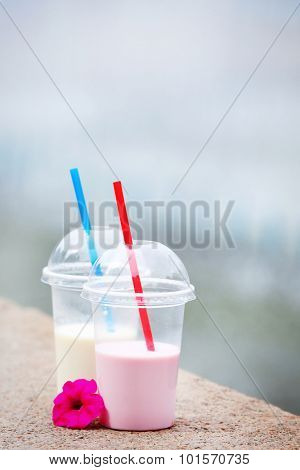 Plastic cups of milkshake on light background, outdoors