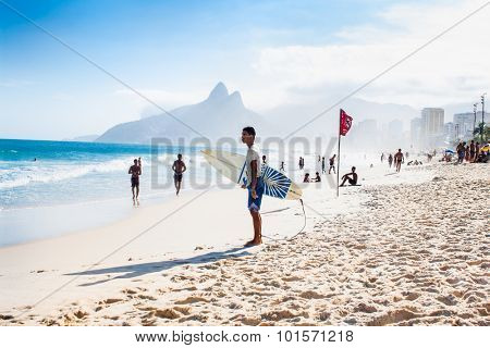 RIO DE JANEIRO, BRAZIL - APRIL 24, 2015: Brazilian surfer walking with surfboard toward Two Brothers Mountain at Ipanema Beach on April 24, 2015, Rio de Janeiro. Brazil.