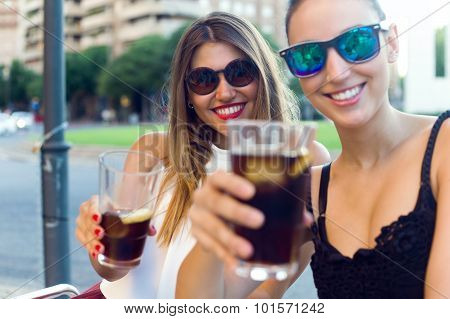 Beautiful Young Women Drinking Refreshment In The Street.
