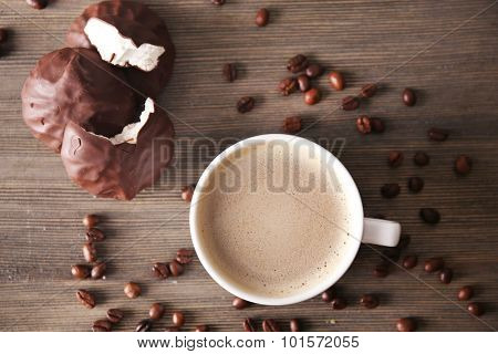 Cup of coffee with zephyr and beans on wooden table, top view