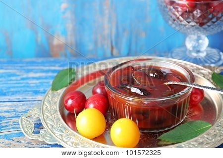 Tasty homemade plum jam in lass saucer on metal tray on wooden background