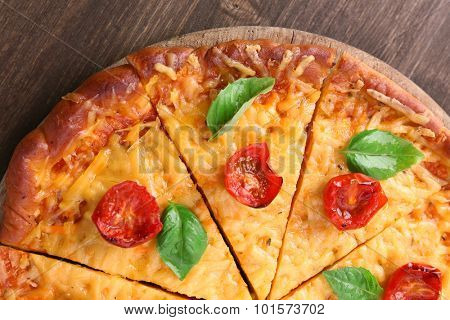 Slices of tasty cheese pizza with basil and cherry tomatoes on table close up