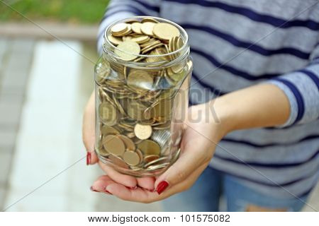Woman holding money jar with coins outdoors