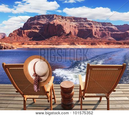 Waves from the boat dissect lakes Powell on the river Colorado. Aft vessels cost two chaise lounges. On a back of one the elegant straw women's hat hangs
