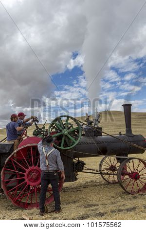 Men working on steam engine.