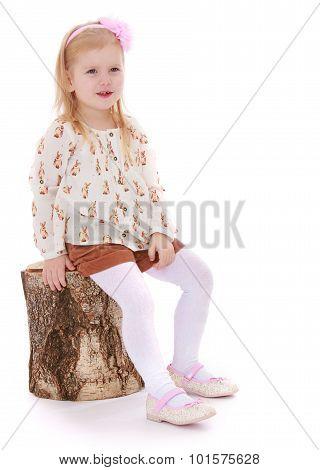 little girl sat down on a stump