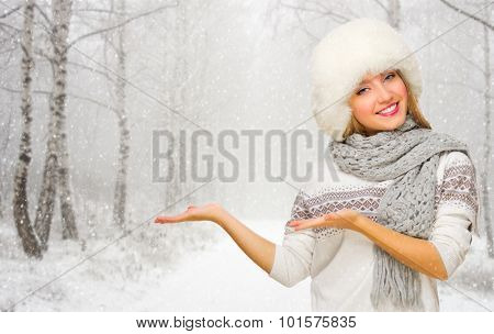 Young smiling girl shows welcome gesture at snowy forest