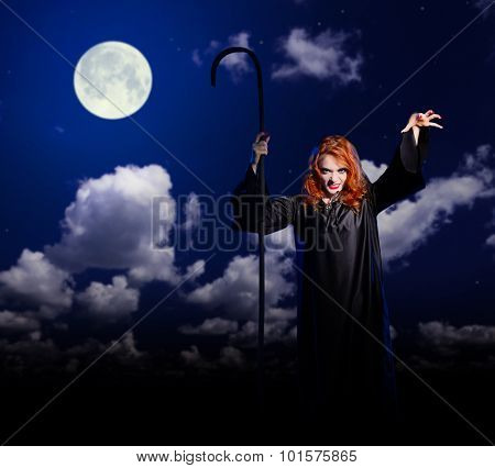 Young witch girl on night sky background