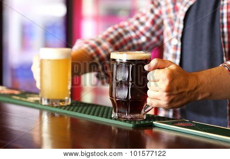 Bartender holding beer glass at workplace