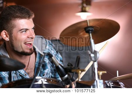 Excited drummer on bright background