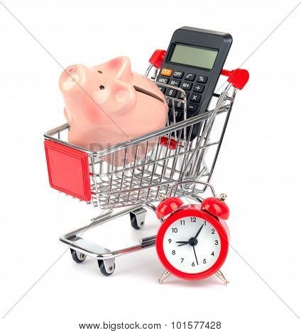 Piggy bank and calculator in shopping cart