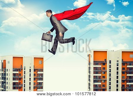 Businessman springing over abyss