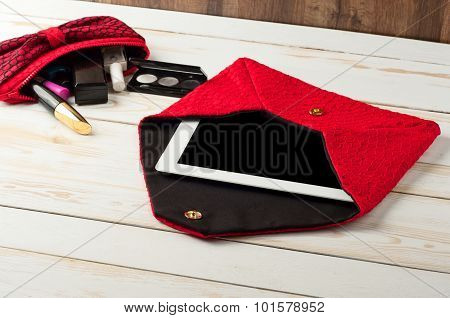Open Red Pen Female Handbag With Tablet Computer In A White Wooden Table