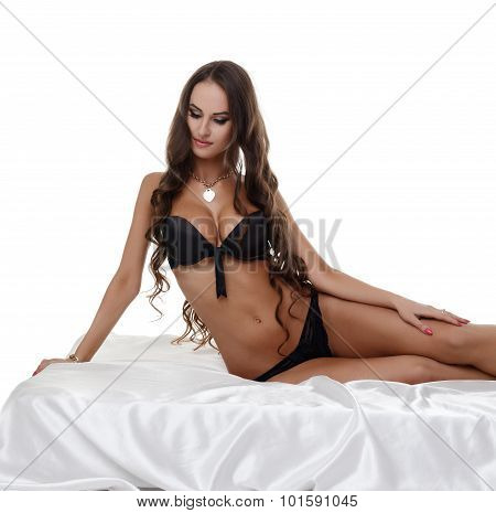Beautiful long-haired model posing in bed