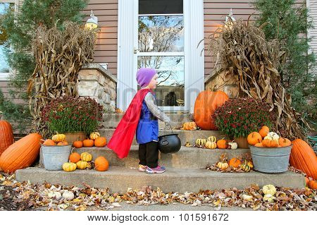 Young Child Standing At House Trick-or-treating On Halloween