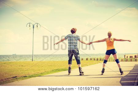 Young Couple On Roller Skates Riding Outdoors