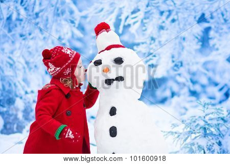 Little Girl Building Snow Man In Winter