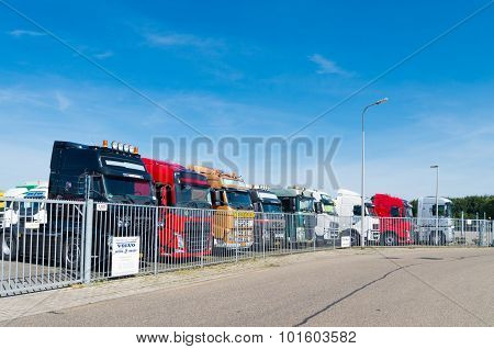 OLDENZAAL NETHERLANDS - AUGUST 1 2015: Row of used volvo trucks for sale behind a gate. Volvo is the world's second largest heavy-duty truck brand.
