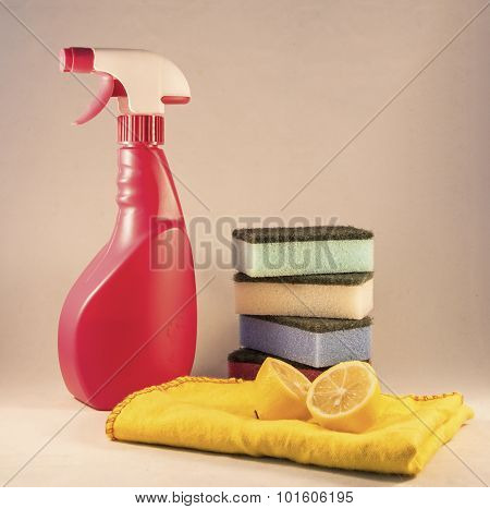 Bottle sponge and lemon with a redish white background