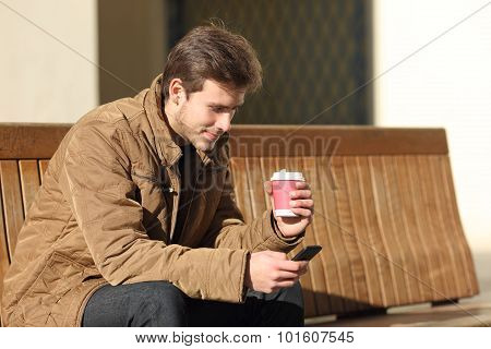 Man Using A Smart Phone And Holding A Coffee Cup