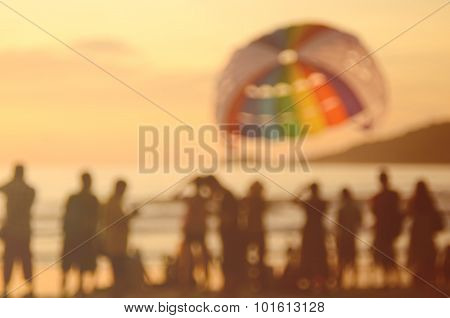 Blur People And Parachute Boat On Beach Abstract Background.