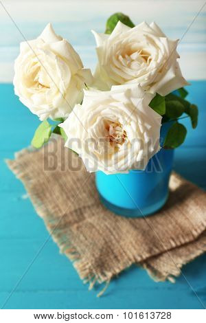 Beautiful white roses on wooden table with sackcloth, closeup