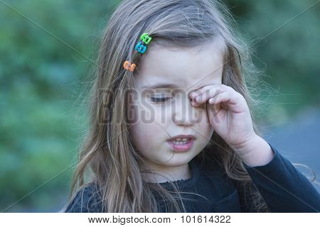 tired or bored little girl wiping her eye