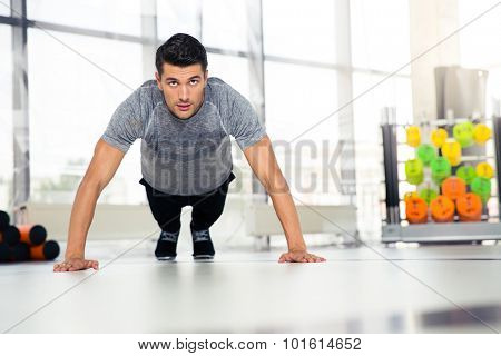 Portrait of a fitness man doing push-ups in gym