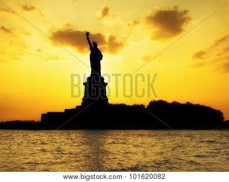 Silhouette of the Statue of Liberty at sunset with reflections on the ocean
