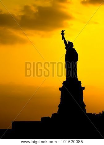 Silhouette of the Statue of Liberty at sunset