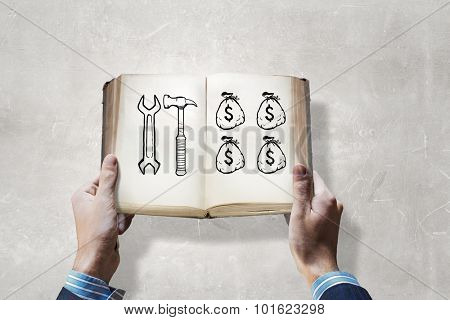 Opened book in male hands with financial ideas on pages
