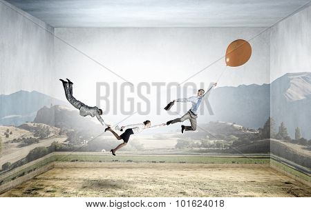 Businesspeople holding each other and flying on colorful balloon