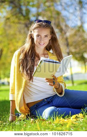 young beautiful schoolgirl sitting in autumn park and reading a book