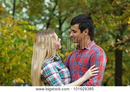 Young loving couple on a date on background of autumn park