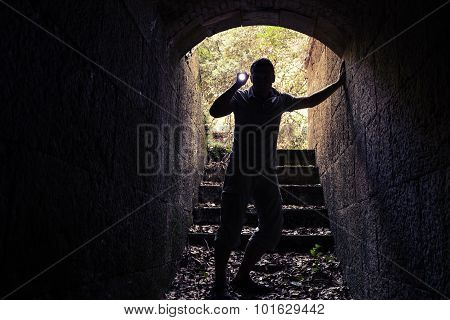 Young Man With Flashlight Enters Dark Stone Tunnel