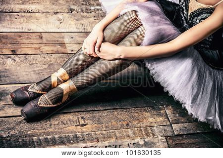 Close-up of slender legs of a ballerina in pointes. Wooden floor. Art concept.