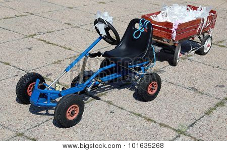 Pedal Go-kart With A Cart With Flakes Stuck To The Bride And Groom