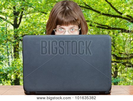 Girl Looks Over Cover Of Laptop And Green Forest