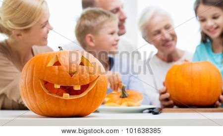 generation, holidays and people concept - helloween pumpkin lantern over happy family at home