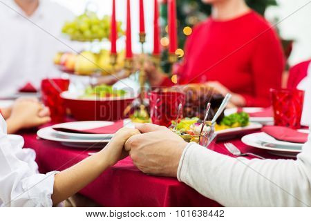 family, holiday, tradition, generation and people concept - close up of family having christmas dinner and holding hands at home